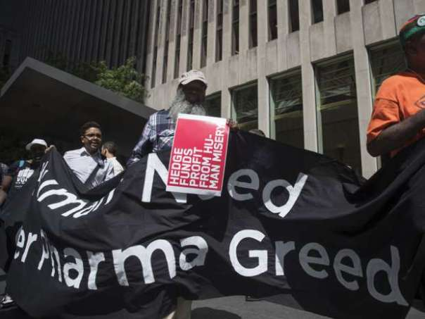 Demonstrators hold up signs during a protest outside the offices of John Paulson, founder of Paulson & Co., not pictured, for his hedge fund's investment in Mylan NV, in New York, U.S, on Tuesday, Aug. 30, 2016. Mylan NV has become the latest pharmaceutical company to provoke nationwide ire for steep price increases. Victor J. Blue/Bloomberg.